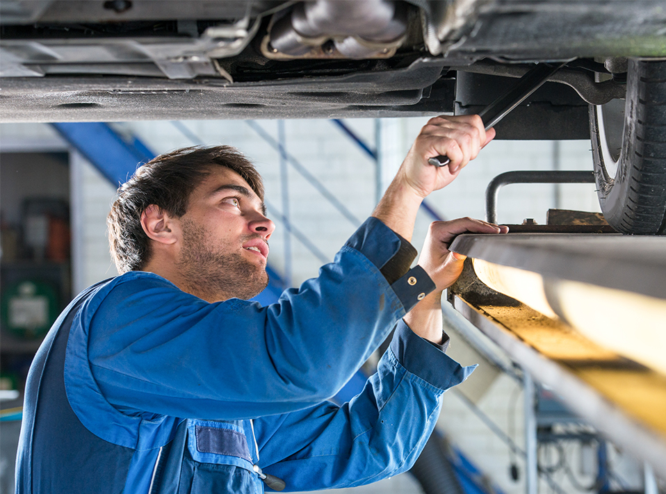 Mechanic checking under a vehicle